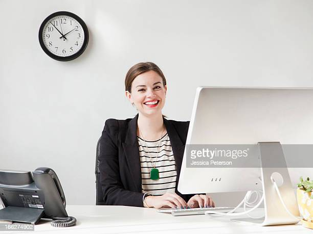 Studio shot portrait of young woman working on computer and smiling