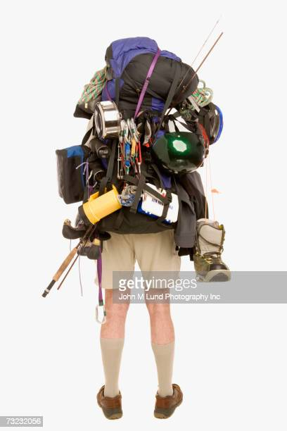 Studio shot rear view of man wearing loaded backpack