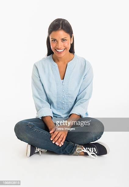 Studio shot woman sitting cross-legged
