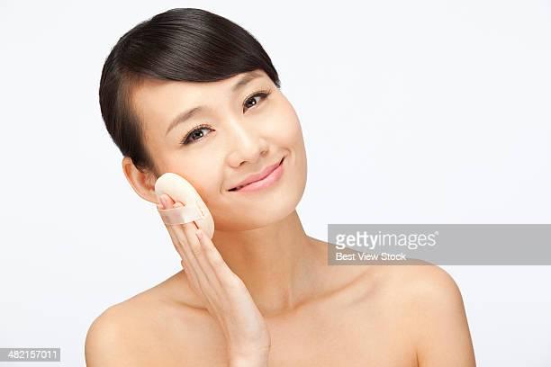 studio shot young woman applying make-up