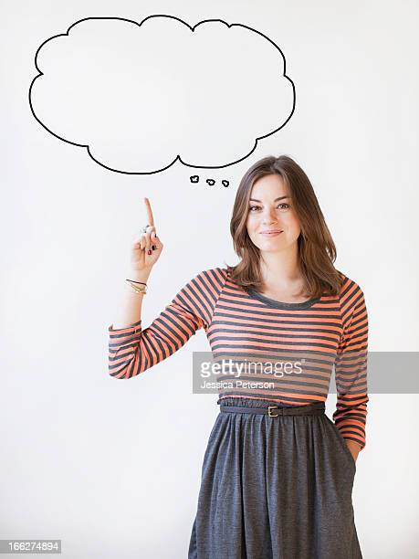 Studio shot young woman pointing up on thought bubble