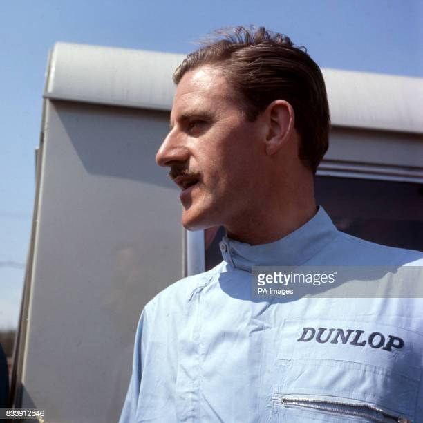 A study of British racing driver Graham Hill in racing overalls