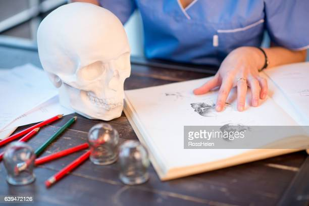 Studying with book and human skull