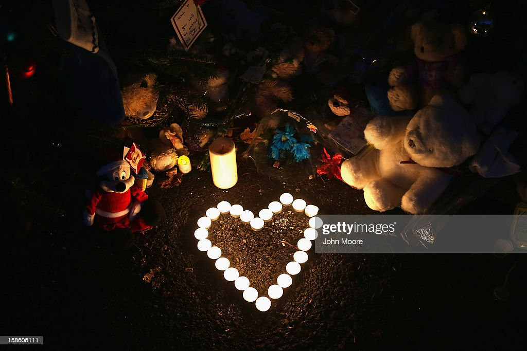 Stuffed animals and a candle arrangement brought by morners adorn a streetside memorial on December 20, 2012 in Newtown, Connecticut. Six funeral services were held Thursday in the Newtown area for some of the 26 students and teachers slain in the attack.