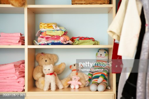Stuffed animals, clothing and towels on shelves in closet : Stock Photo