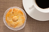 Small stuffed chicken pie known as Empada in Brazil and Portugal. Snack and cup of coffee on wood, overhead.