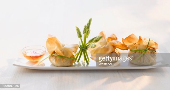 Stuffed dim sum bag and sweet chili sauce decorated with wild asparagus on plate : Stock Photo