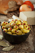 Stuffed green olives on rustic wood background.
