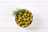 bowl of green olives stuffed with red pepper on white background