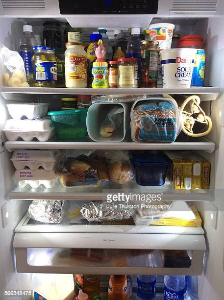 A stuffed not too organized opened refrigerator filled with dairy products like eggs and sour cream and other food products like bread juice water...