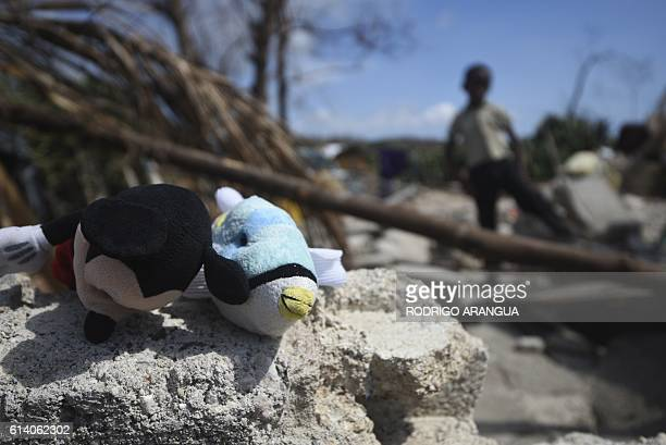 Stuffed toys are seen as a boy stands in a home destroyed by Hurricane Matthew in Port Salut southwest of PortauPrince on October 11 2016 Haiti faces...