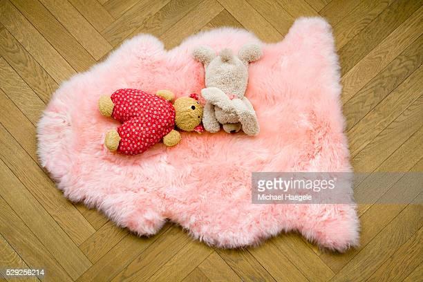 Stuffed Toys on Pink Sheepskin Rug