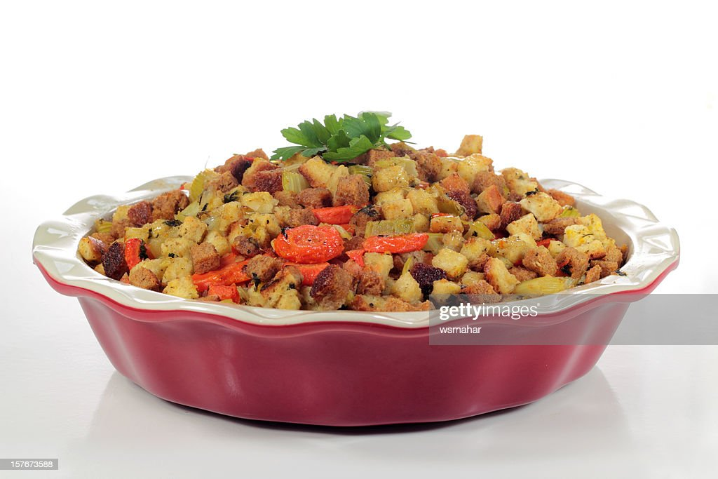 Stuffing being served in a red casserole dish