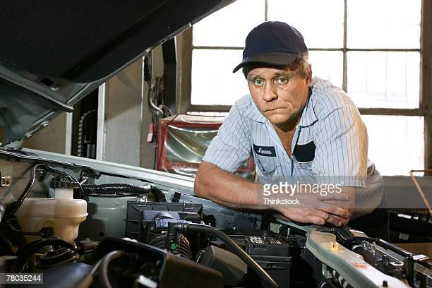 Stumped mechanic leaning over engine compartment