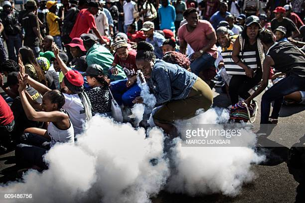 TOPSHOT A stun grenade thrown by South African police forces ricochet on a student taking part in a protest in Johannesburg on September 21 2016...