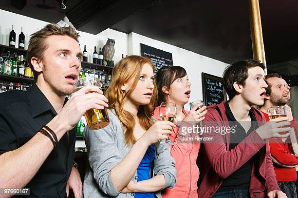 stunned open mouthed sport fans in a bar