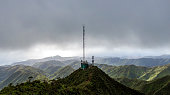Stunning aerial drone view of a communications tower at the summit end of famous Wiliwilinui Ridge Hiking Trail near Honolulu on the island of Oahu, Hawaii. Coastline in the background & cloud cover.