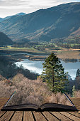 Beautiful Autumn Fall landscape image of view from route to Walla Crag near Derwent Water in Lake District coming out of pages of open story book