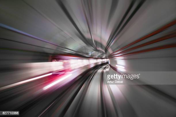 Stunning long exposure view traveling inside futuristic tunnel with red colors and train in motion with huge sensation of speed during the connection of Barcelona city with the airport.