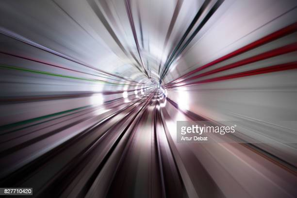 Stunning long exposure view traveling inside futuristic tunnel with red colors and cable connections with huge sensation of speed during the connection of Barcelona city with the airport.