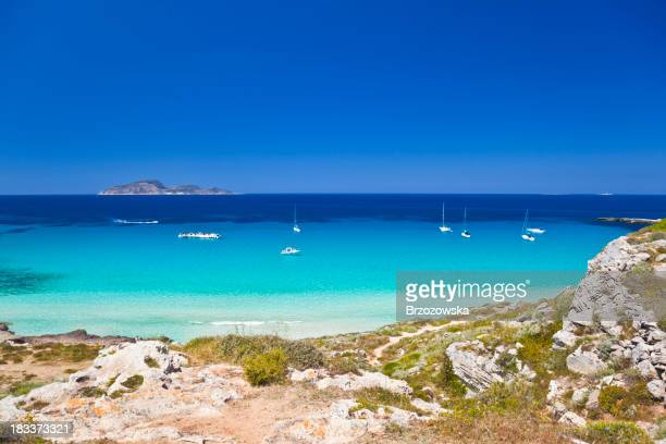 Stunning Mediterranean beach view with several sailing boats