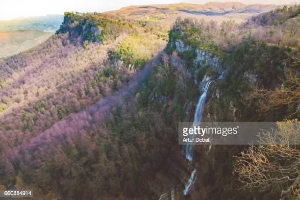 Stunning mountain landscape with wild waterfall in a colorful forest nature view in the Collsacabra mountain of the Catalonia region during a hike travel in the zone.