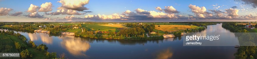 Stunning panoramic landscape with clouds reflected in tranquil river