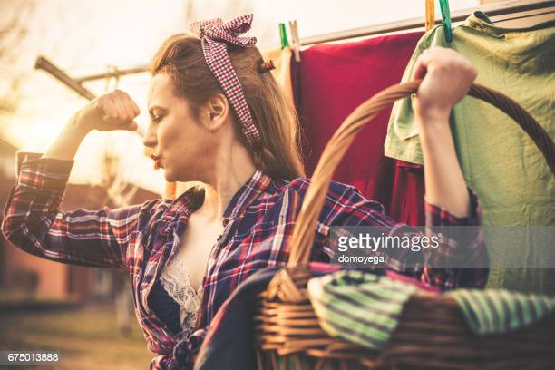 Stunning pin-up girl doing laundry and carrying laundry basket