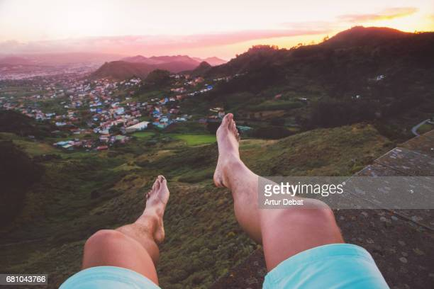 Stunning sunset landscape over the Tenerife island taken from elevated viewpoint with guy legs and personal perspective sitting during travel vacations in the island.
