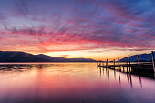 A photograph taken at the Ashness Gate jetty/pier at Derwentwater in Keswick, Lake District, UK. The photograph features a vibrant orange and purple sunset, the beautiful Cumbrian mountains in the bac