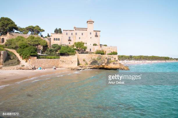 Stunning view of castle in front of the sea with cool beach during summer vacations in the Catalonia region.