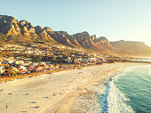 Stunning wide angle aerial drone evening view of Camps Bay, an affluent suburb of Cape Town, Western Cape, South Africa. Twelve apostles mountain range in the background. Photo cross processed.