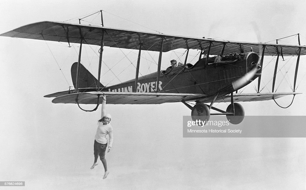 Stunt flier Lillian Boyer hangs from the wing of a biplane in midair during an aerobatic performance.