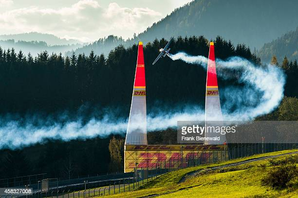 ZELTWEG STEIERMARK AUSTRIA A stunt flying aeroplane releasing smoke is flying through 2 pylons during the Red Bull Air Race