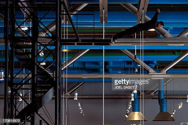 A stunt jumps on June 18 from a tower set by French artist Loris Greaud as part of a show entitled 'I' like electrical intensity and like the English...