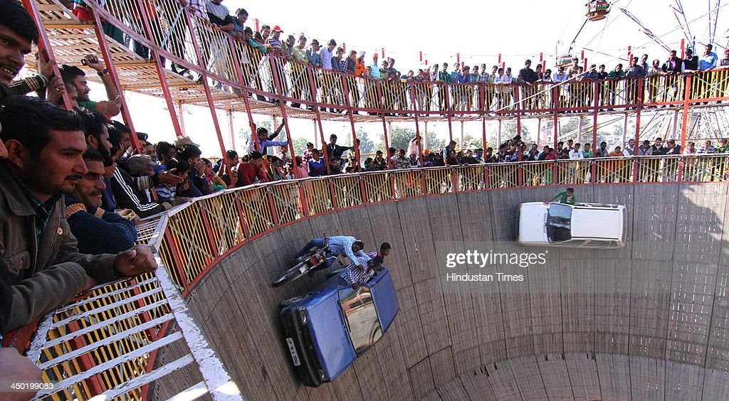 Stunt men ride their cars as they display their skills during the famous Jhiri fair - a village where 'blessed peasant Jitu' scarified his life fighting for the rights of tillers at Kanachak village on November 17, 2013 in Jammu, India. According to legend, the fair is held in memory of Baba Jitu, a simple and honest farmer who killed himself since he was not prepared to submit to the unjust demands of a landlord who wanted him to part with his crop.