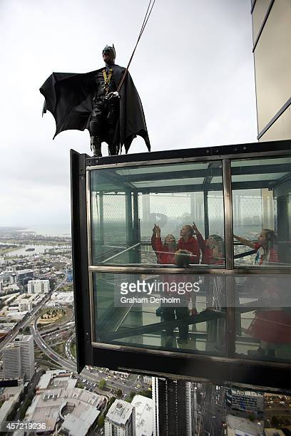 Stuntman Chris Davies scales the outside of the Eureka Tower dressed as Batman as young school children look on at Eureka Skydeck on October 15 2014...