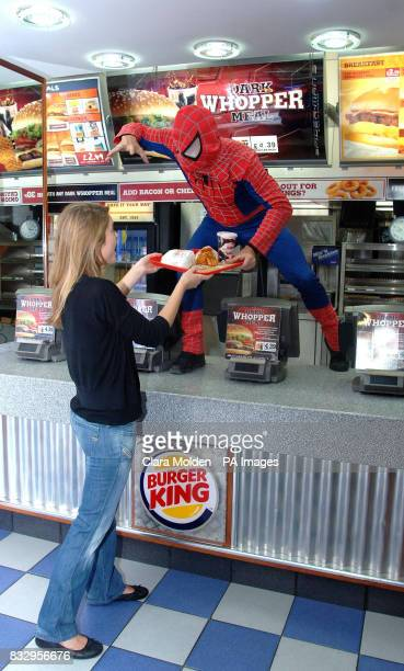 Stuntman Steen Young dressed as Spiderman serves Jo Dyson a Dark Whopper in Burger King in Leicester Square central London prior to tonight's...