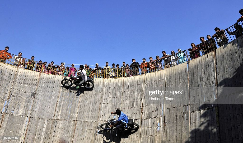 Stuntmen perform on bike as villagers watch the show of Maut ka Kuan or Well of Death during the famous Jhiri fair - a village where 'blessed peasant Jitu' scarified his life fighting for the rights of tillers at Kanachak village on November 18, 2013 in Jammu, India. According to legend, the fair is held in memory of Baba Jitu, a simple and honest farmer who killed himself since he was not prepared to submit to the unjust demands of a landlord who wanted him to part with his crop.