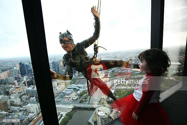 Stuntwoman Rowena Davies scales the outside of the Eureka Tower dressed as Catwoman as childhood heart disease sufferer Maisy Bodinnar looks on at...