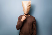 Stupid young man with a brown paper bag over his head