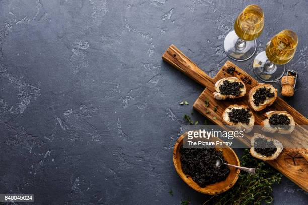 Sturgeon black caviar in wooden bowl, sandwiches and champagne on dark stone background copy space
