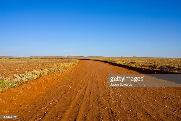 A red sandy track winds over a rugged plain in a remote outback desert