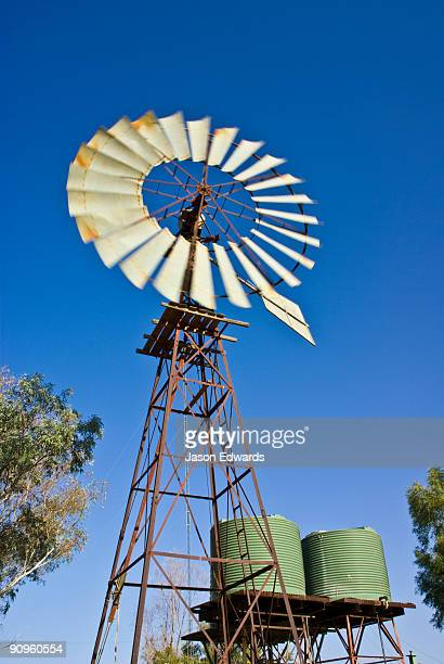 Windmills pump water reserves beneath the desert for outback stations.