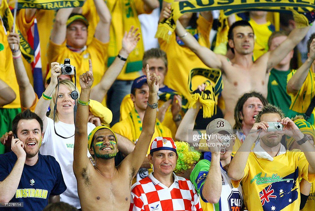 A Croatian fan looks dejected as Australian fans jubilate at the end of the World Cup 2006 group F football match Croatia vs Australia, 22 June 2006 at Stuttgart stadium. Match ended 2-2.