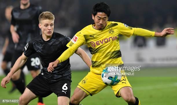 Stuttgart's Argentinian midfielder Santiago Ascacibar and Dortmund's Japanese midfielder Shinji Kagawa vie for the ball during the German first...