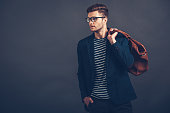 Confident young handsome man in glasses holding bag and looking away while standing against grey background