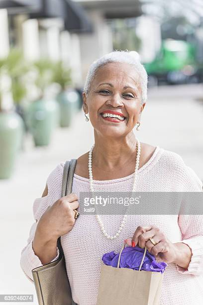 Stylish African American woman on sidewalk, out shopping