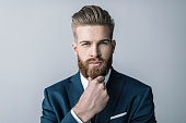 Stylish bearded businessman with hand on chin looking at camera