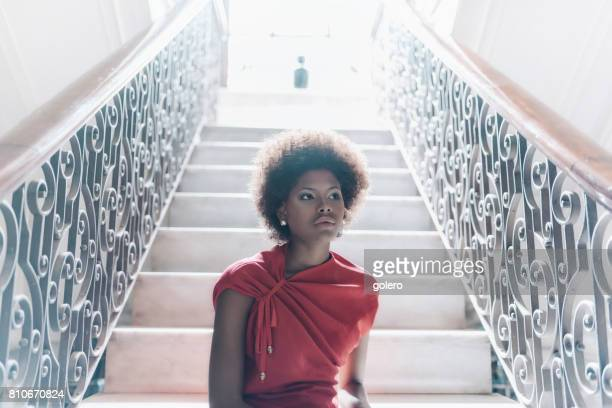 stylish beautiful young cuban woman sitting on stairs indoors